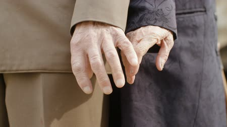 kapcsolat : Cinematic close-up of two elderly people of advanced age, men and women in vintage clothing, connecting the hands. The concept of world war II survivors