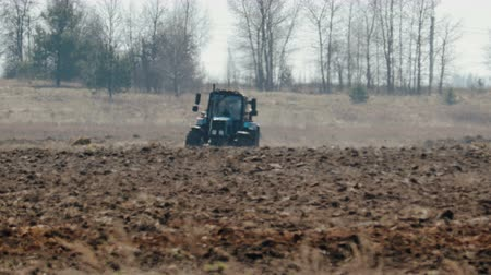 plough land : Static shot of a blue tractor with big black wheels and a powerful grouser, heavy plowing the dark fertile soil. The warmth from the ground and the motor distorts the image Stock Footage