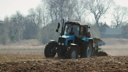 жесткий : Static shot of a blue tractor with big black wheels and a powerful grouser, heavy plowing the dark fertile soil. The warmth from the ground and the motor distorts the image Стоковые видеозаписи