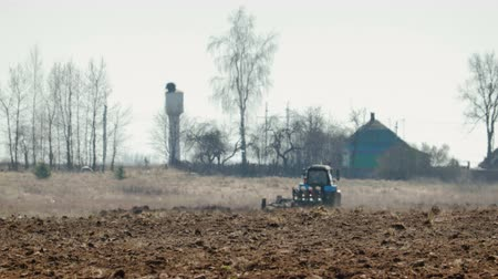 solo : Static shot of a blue tractor with big black wheels and a powerful grouser, heavy plowing the dark fertile soil. The farm machine is followed by white birds. The warmth from the ground and the motor distorts the image