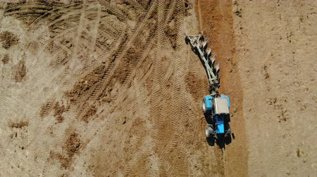 solo : Aerial view of a blue tractor with four ploughshares plowing dry fertile land of brown color. The concept of farming, agriculture. Parallax camera, the object is stationary relative to the background Stock Footage