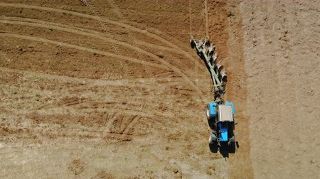 bělorusko : Aerial view of a blue tractor with four ploughshares plowing dry fertile land of brown color. The concept of farming, agriculture. Parallax camera, the object is stationary relative to the background Dostupné videozáznamy