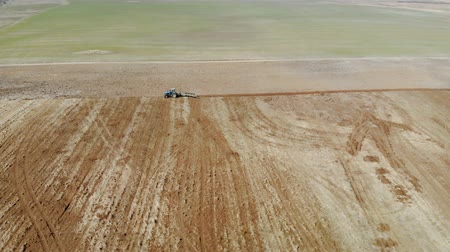 batatas : Blue, vintage tractor cultivates the soil. Shooting from a birds eye view, beautiful landscape Stock Footage