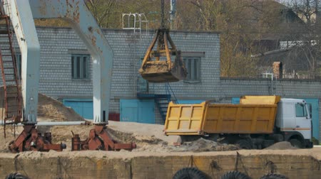 ciężarówka : Static shot port crane near the river, unloading sand from the grab bucket in the truck, dump truck with a yellow body and a white cabin. The concept of road construction Wideo