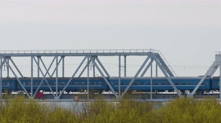 perspektif : Static shot of a train with blue passenger cars passing over the bridge with metal supports against the sky