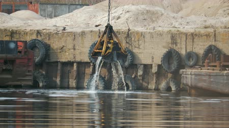 vessels : The grab bucket of the excavator rises from the river in the port against the background of an old, rusty, vintage barge and car tires. The device gets out of the water with splashes. Cleaning the bottom of the pond