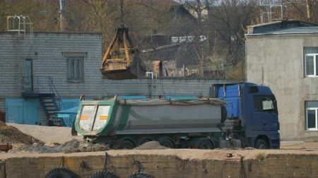 ciężarówka : Static shot port crane near the river, unloading sand from the grab in the truck, dump truck with a blue cabin. The concept of road construction