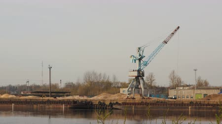 механический : Interval shooting of the port crane lowering and lifting the grab bucket into the water, the river, against the background of two moving barges, a lot of people, a yellow loader and a blue train