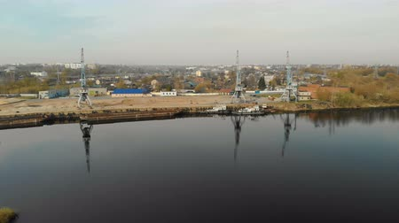vessels : Aerial view of three cranes with reflection in the water in the river port with barges and tugs on the background of the city