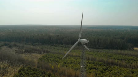 винты : Circular flight of a single wind generator with a rotating three-bladed propeller, a propeller installed in a forest in clear Sunny weather. Aerial view. Renewable energy source