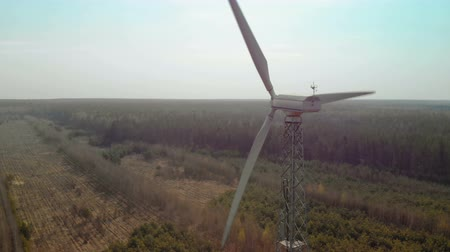 trzy : Circular flight of a single wind generator with a rotating three-bladed propeller, a propeller installed in a forest in clear Sunny weather. Aerial view. Renewable energy source