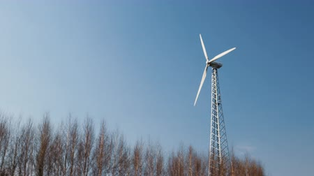 uç : A powerful wind turbine with the rotation of the three rotor blades and changing the position of the installation in the wind against the tops of trees and blue sky. The concept of alternative clean energy sources