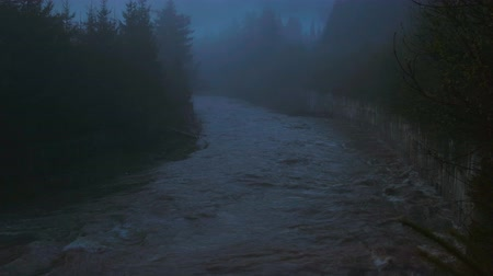 crepúsculo : Gloomy landscape with a mountain, bubbling river. Rocky river Bank. Dark blue color of the water. Eerie atmosphere in cloudy rainy weather. The style of horror. 4k