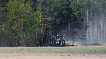 powerful : A powerful red tractor processes dusty brown soil with a disc harrow attached to the background of a coniferous forest. Heat from the ground and the machine distorts the image Stock Footage