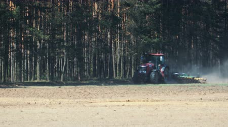 боке : A powerful red tractor processes dusty brown soil with a disc harrow attached to the background of a coniferous forest. Heat from the ground and the machine distorts the image Стоковые видеозаписи