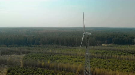 uç : Circular flight of a single wind generator with a rotating three-bladed propeller, a propeller installed in a forest in clear Sunny weather. Aerial view. Renewable energy source