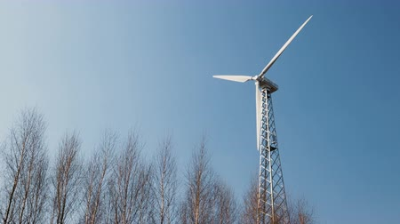 trzy : A powerful wind turbine with the rotation of the three rotor blades and changing the position of the installation in the wind against the tops of trees and blue sky. The concept of alternative clean energy sources