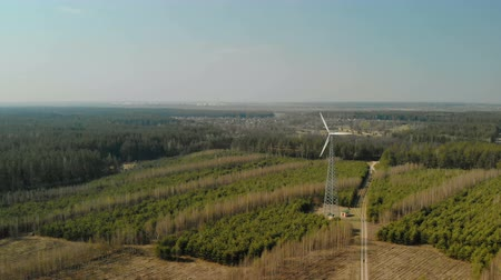 uç : Single wind turbine with rotating three-bladed propeller installed in the forest in clear Sunny weather. Aerial view. Renewable energy source Stok Video