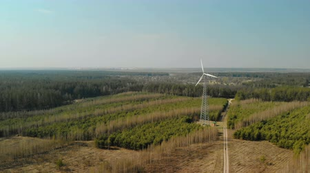 trzy : Single wind turbine with rotating three-bladed propeller installed in the forest in clear Sunny weather. Aerial view. Renewable energy source Wideo