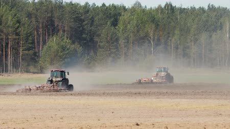 solo : Rear side view of two powerful tractors plowing, cultivating dry soil in hot Sunny weather against a coniferous forest. From under the agricultural devices rise clouds of dust, heat from the ground and technology distorts the image