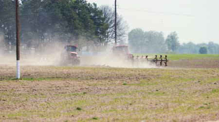 боке : Two tractors of red color processing the soil in hot dry weather on a background of poles of a power line. Many birds are flying in the foreground