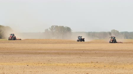 trzy : Three tractors processing the dusty arid soil of brown color against the coniferous forest. The concept of abnormal weather for agriculture
