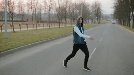 kolumna : Handheld slomotion shot a young, handsome, energetic guy in black pants and a blue hooded vest performing somersaults and dance on the roadway Wideo