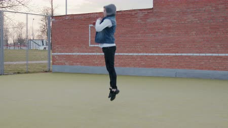 vista lateral : A static shot of a side view of a young, handsome, energetic guy, a street dancer in black pants and a blue hooded vest performing lowering to the ground and getting to his feet Stock Footage