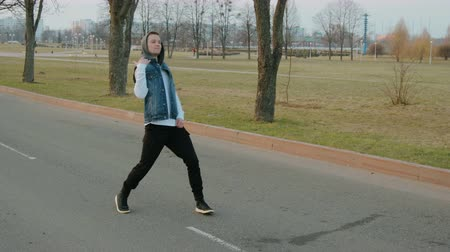 vibráló : Steadicam shot of a young, handsome, energetic guy in black pants and a blue hooded vest performing a hip hop dance on the roadway with white markings Stock mozgókép