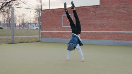 hiphop : A static shot of a young, handsome, energetic guy, a street dancer in black pants and a blue hooded vest performing an acrobatic element, a handstand and rising to the surface, on a Playground with a green lawn