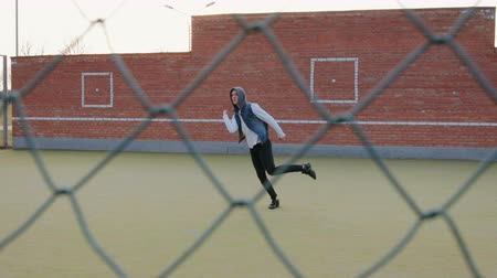 hekje : Dolly shot a young energetic guy, a street dancer, in black pants and a white sweater performing beautiful, mesmerizing moves on the Playground with a metal mesh fence in the foreground