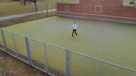 adolescente : Aerial view a young energetic guy, a street dancer, in black pants and a white sweater performing beautiful, mesmerizing moves on the Playground with a metal mesh fence in the foreground
