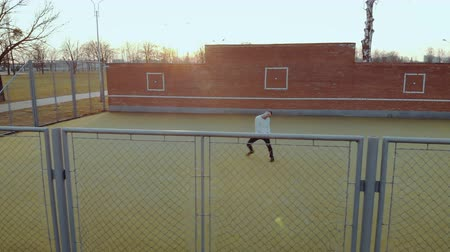 hekje : Aerial view a young energetic guy, a street dancer, in black pants and a white sweater performing beautiful, mesmerizing moves on the Playground with a metal mesh fence in the foreground