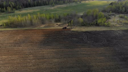 powerful : Aerial view on the side of a powerful red tractor with a plow, agricultural machine, performing processing, plowing, cultivation of dark soil on the background of a magnificent picturesque nature Stock Footage