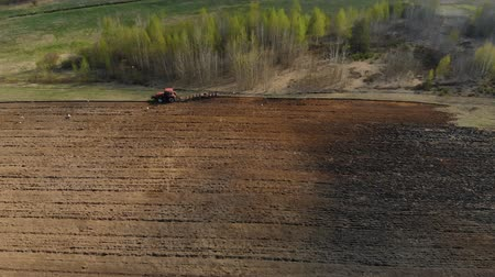 fertility : Aerial view on the side of a powerful red tractor with a plow, agricultural machine, performing processing, plowing, cultivation of dark soil on the background of a magnificent picturesque nature Stock Footage