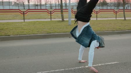 riskli : Steadicam shot, flying around the circle of a young modern guy in a white jacket and a blue denim vest with a hood performing a handstand on the roadway with markings
