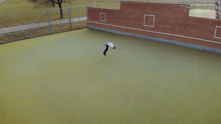 hiphop : Aerial view of a young, beautiful, energetic guy, a street dancer in black pants and a white sweater performing an acrobatic element, a handstand and rising to the surface, on a Playground with a green lawn