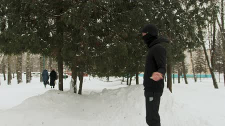 lano : Steadicam shot of a young guy in a black mask on his face, in a sports suit performing exercises, jumping rope in a snow-covered Park outdoors in frosty weather. The concept of winter sports, healthy lifestyle