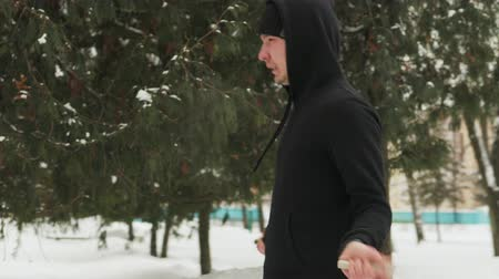 lano : Steadicam shot of a young guy in a black tracksuit performing exercises, jumping rope in a snow-covered Park outdoors in frosty weather. The mans mouth is steaming. The concept of winter sports, healthy lifestyle Dostupné videozáznamy