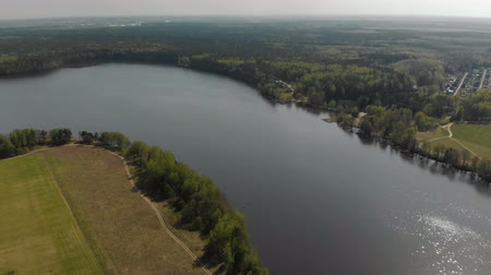 enrolamento : Beautiful view of the forest, winding river in the city. The water in the river glistens in the sun. Near the river field Stock Footage