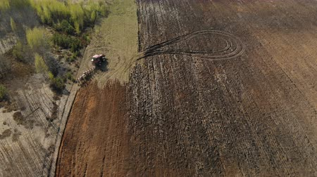 plowed land : Agricultural machine with a plow plowing the soil, preparing the land for planting on the background of beautiful nature. Aerial filming
