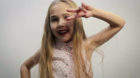 mókás : Close-up of a funny girl, a child, a blonde in a light shirt with a pink pea pattern, performing dance movements with her body and hands on a white background. The concept of good mood, holiday feeling Stock mozgókép