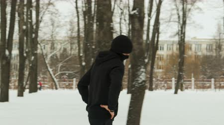 vista lateral : Steadicam shot is a side view of a young guy in black sportswear and a Balaclava performing a warm-up before training in a winter snow-covered city Park. The concept of hardening fighter, puncher, lover of martial arts