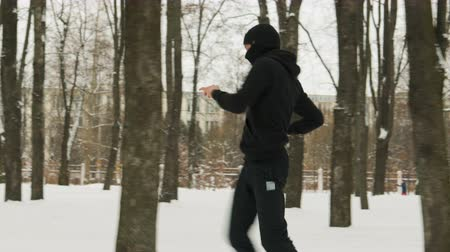 vista lateral : Steadicam shot is a side view of a young guy in black sportswear and a Balaclava performing a warm-up before training in a winter snow-covered city Park. Man waving his legs. The concept of hardening fighter, puncher, lover of martial arts Stock Footage