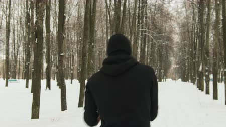kardio : Steadicam shot rear view of a young guy in black sportswear with a hood performing a hand-held workout in a winter snow-covered city Park. The concept of hardening fighter, puncher, lover of martial arts
