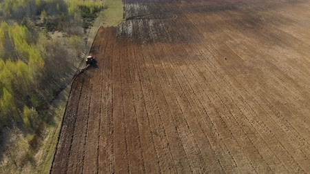 tillage : Agricultural machine with a plow plowing the soil, preparing the land for planting on the background of beautiful nature. Aerial filming