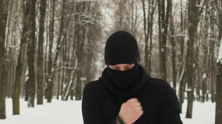 pudełko : Steadicam shot a front view of a young guy in black sportswear with a hood and a ninja Balaclava performing punches in motion in a winter snow-covered city Park. The concept of hardening fighter, puncher, martial arts lover Wideo