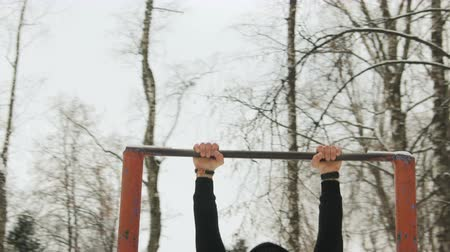 balaclava : Steadicam shot of a young guy in black sportswear and Balaclava, a ninja mask performing pull-UPS, body lift with a coup on an old vintage bar in a snowy winter city Park among the trees. The concept of a healthy lifestyle