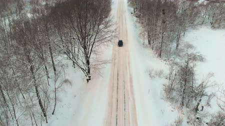 kavrama : Aerial view of the car in black with the included marker lights, driving on a snowy winter road among the trees with bare branches in the countryside