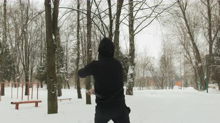 arma : A handsome young man in a black suit and balaclava demonstrates mastery with nunchucks in an outdoor winter park. Goes in for sports and has fun Filmati Stock